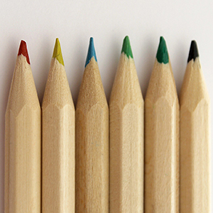 Six differently coloured, sharp pencils in a row
